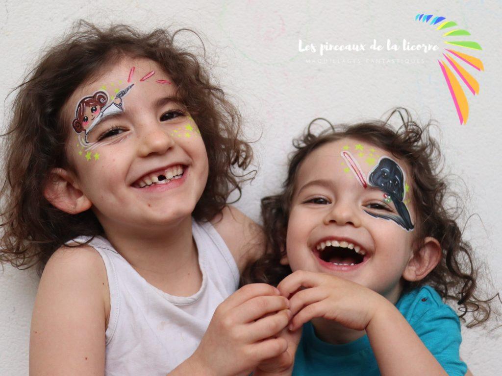 Deux enfants souriants avec des maquillages Princesse Leia et Dark Vador Star wars